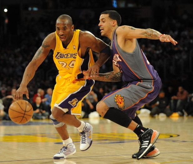 LOS ANGELES, CA - DECEMBER 10:  Kobe Bryant #24  of the Los Angeles Lakers dribbles around Matt Barnes #22 of the Phoenix Suns during the second half at the Staples Center on December, 10 2008 in Los Angeles, California.   NOTE TO USER: User expressly ack