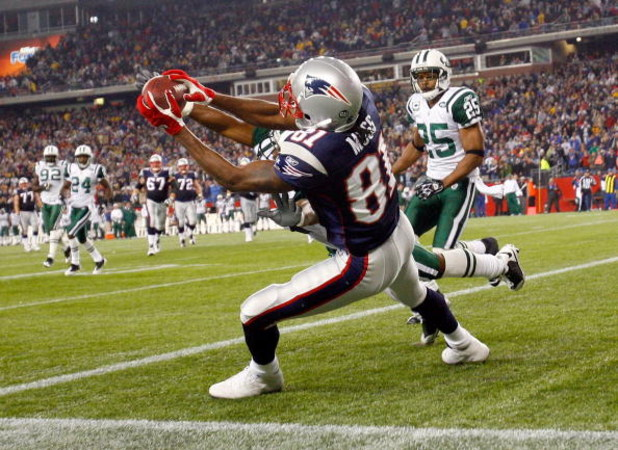 FOXBORO, MA - NOVEMBER 13:  Randy Moss #81 of the New England Patriots catches a touchdown pass against the defense of Ty Law #22 and Kerry Rhodes #25 of the New York Jets, sending the game to overtime at Gillette Stadium on November 13, 2008 in Foxboro,