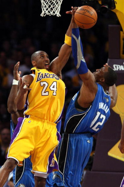 LOS ANGELES, CA - JUNE 04:  Kobe Bryant #24 of the Los Angeles Lakers reaches for a rebound against Dwight Howard #12 of the Orlando Magic in Game One of the 2009 NBA Finals at Staples Center on June 4, 2009 in Los Angeles, California. NOTE TO USER: User