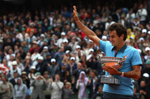 PARIS - JUNE 07:   Roger Federer of Switzerland salutes the fans as he holds the trophy following victory during the Men's Singles Final match against Robin Soderling of Sweden on day fifteen of the French Open at Roland Garros on June 7, 2009 in Paris, F