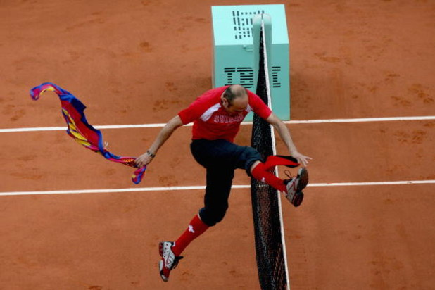 PARIS - JUNE 07:  An intruder jumps the net after interfering with Roger Federer of Switzerland during the Men's Singles Final match between Robin Soderling of Sweden and Roger Federer of Switzerland on day fifteen of the French Open at Roland Garros on J