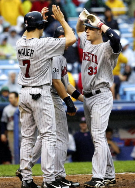 NEW YORK - SEPTEMBER 2:  Justin Morneau #33 of the Minnesota Twins is met at home by teammates Michael Cuddyer #5 and Joe Mauer #5 after hitting a three run home run in the eigth inning against the New York Yankees at Yankee Stadium September 2, 2006 in t