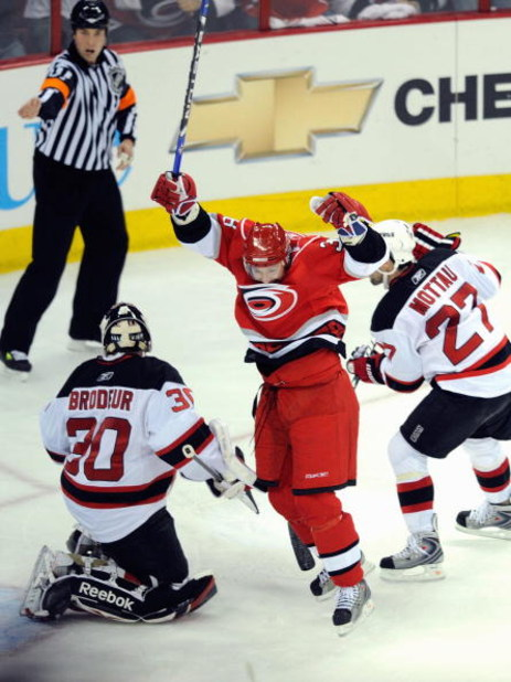 RALEIGH, NC - APRIL 21:  Jussi Jokinen #36 of the Carolina Hurricanes celebrates his goal against goalie Martin Brodeur #30 and Paul Martin #7 of the New Jersey Devils during Game Four of the Eastern Conference Quarterfinals of the 2009 Stanley Cup Playof