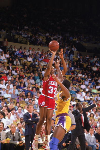 LOS ANGELES - 1989:  Hersey Hawkins #33 of the Philadelphia 76ers shoots over Magic Johnson #32 of the Los Angeles Lakers during the 1989-1990 NBA season game at the Great Western Forum in Los Angeles, California.  (Photo by Ken Levine/Getty Images)