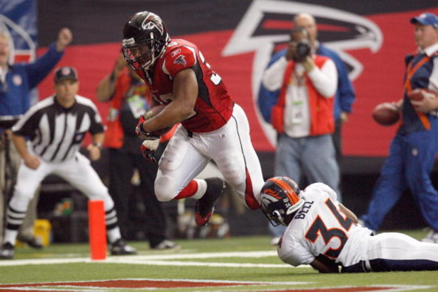 ATLANTA - NOVEMBER 16:  Michael Turner #33 of the Atlanta Falcons runs in for a touchdown against Josh Bell #34 of the Denver Broncos at the Georgia Dome on November 16, 2008 in Atlanta, Georgia.  (Photo by Kevin C. Cox/Getty Images)