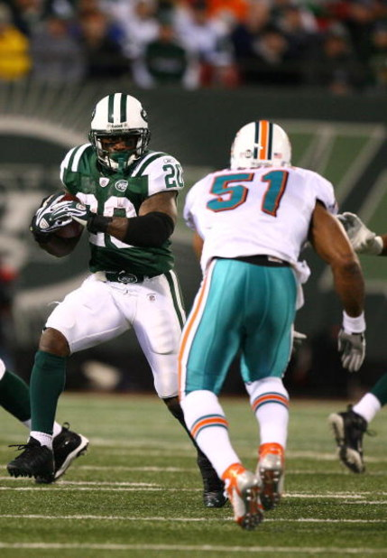 EAST RUTHERFORD, NJ - DECEMBER 28:  Thomas Jones #20 of The New York Jets runs the ball as Akin Ayodele #51 of The Miami Dolphins attempts the tackle during their game on December 28, 2008 at Giants Stadium in East Rutherford, New Jersey.  (Photo by Al Be