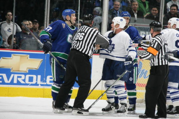 VANCOUVER - JANUARY 10:  Jarkko Ruutu #37 of the Vancouver Canucks and Tie Domi #28 of the Toronto Maple Leafs are seperated by the linesman during the NHL game on January 10, 2006 at General Motors Place in Vancouver, Canada. The Canucks defeated the Map