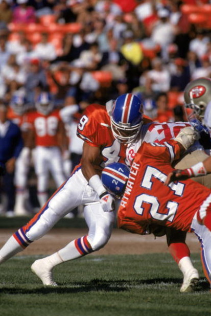 SAN FRANCISCO - AUGUST 3:  Safeties Dennis Smith #49 and Steve Atwater #27 of the Denver Broncos team up for a tackle during pre season game against the San Francisco 49ers at Candlestick Park on August 3, 1992 in San Francisco, California.  The 49ers won