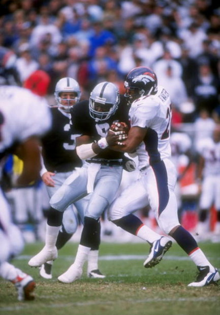 19 Oct 1997: Safety Steve Atwater of the Denver Broncos (right) tries to bring down wide receiver Tim Brown of the Oakland Raiders (center) during a game at the Oakland Alameda County Coliseum in Oakland, California. The Raiders won the game 28-25.