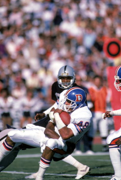 LOS ANGELES - NOVEMBER 2:  Safety Dennis Smith #49 of the Denver Broncos catches a pass during a game against the Los Angeles Raiders at the Los Angeles Memorial Coliseum on November 2, 1986 in Los Angeles, California.  The Broncos won 21-10.  (Photo by G