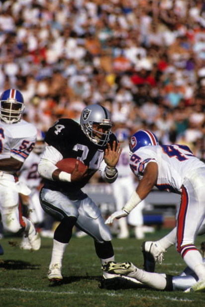 LOS ANGELES - DECEMBER 4:  Running back Bo Jackson #34 of the Los Angeles Raiders looks to make a move against Denver Broncos safety Dennis Smith #49 during a game at the Los Angeles Memorial Coliseum on December 4, 1988 in Los Angeles, California. The Ra