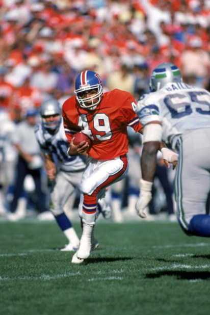 DENVER - SEPTEMBER 13:  Safety Dennis Smith #49 of the Denver Broncos runs back an interception during a game against the Seattle Seahawks at Mile High Stadium on September 13, 1987 in Denver, Colorado.  The Seahawks won 17-10.  (Photo by George Rose/Gett