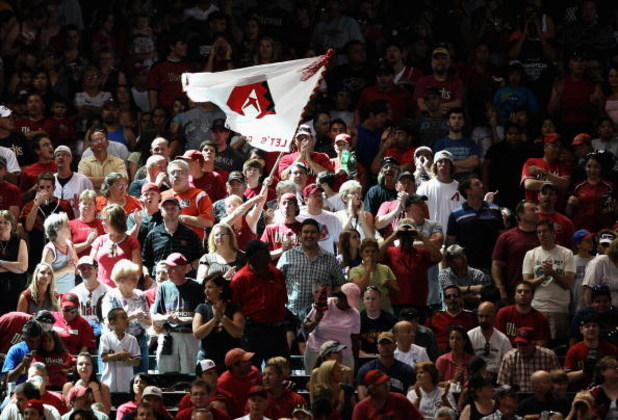 PHOENIX - MAY 30:  Fans of the Arizona Diamondbacks cheer and wave a team flag during the tenth inning of the major league baseball game against the Atlanta Braves at Chase Field on May 30, 2009 in Phoenix, Arizona. The Diamondbacks defeated the Braves 3-