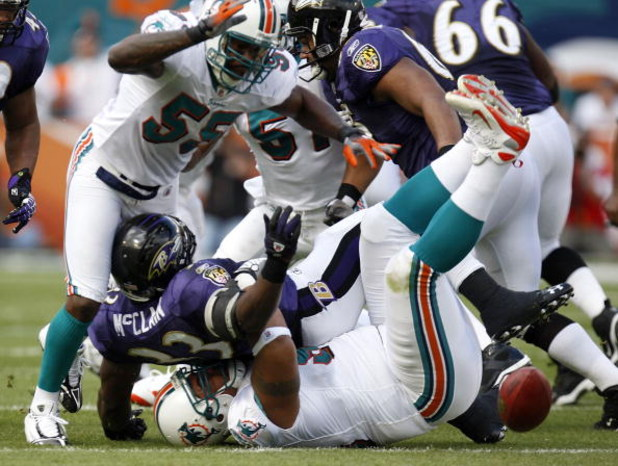 MIAMI - JANUARY 04:  Le'Ron McClain #33 of the Baltimore Ravens fumbles on a first quarter run while being tackled by Paul Soliai #96 and Joey Porter #55 of the Miami Dolphins during their AFC Wild Card playoff game on January 4, 2009 at Dolphin Stadium i