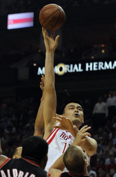 HOUSTON - APRIL 30:  Center Yao Ming #11 of the Houston Rockets takes a shot against Joel Przybilla #10 and LaMarcus Aldridge of the Portland Trail Blazers in Game Six of the Western Conference Quarterfinals during the 2009 NBA Playoffs at Toyota Center o