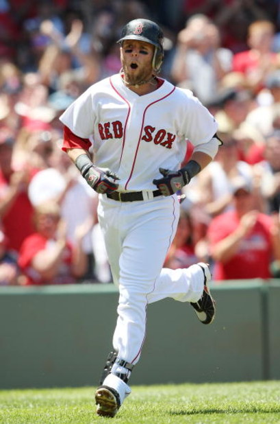 BOSTON - JULY 05:  Dustin Pedroia #15 of the Boston Red Sox celebrates his solo home run in the first inning against the Seattle Mariners on July 5, 2009 at Fenway Park in Boston, Massachusetts.  (Photo by Elsa/Getty Images)
