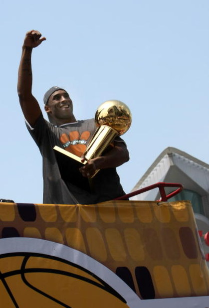 LOS ANGELES, CA - JUNE 17:  Kobe Bryant #24 holds the Larry O'Brien trophy and waves to the crowd from the top of a double decker bus at the start of the Los Angeles Lakers NBA championship victory parade outside the Staples Center on June 17, 2009 in Los