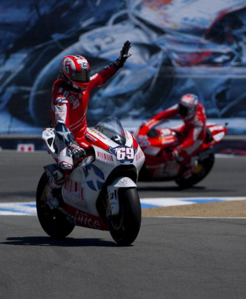MONTEREY, CA - JULY 5:  Nicky Hayden rider of the #69 Ducati waves to the crowd as his teamate Casey Stoner rides in the background after the Moto GP Red Bull U. S. Grand Prix at the Mazda Raceway Laguna Seca on July 5, 2009 in Monterey, California.  (Pho