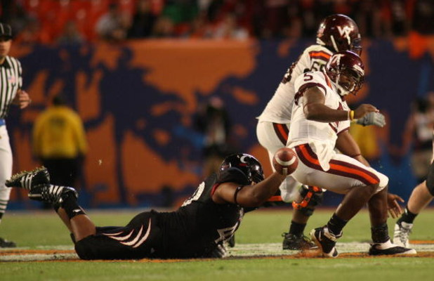MIAMI - JANUARY 01:  John Hughes # 40 of the Cincinnati Bearcats tackles Tyrod Taylor #5 of the Virginia Tech Hokies as he loses the ball during the FedEx Orange Bowl at Dolphin Stadium on January 1, 2009 in Miami, Florida.  (Photo by Marc Serota/Getty Im
