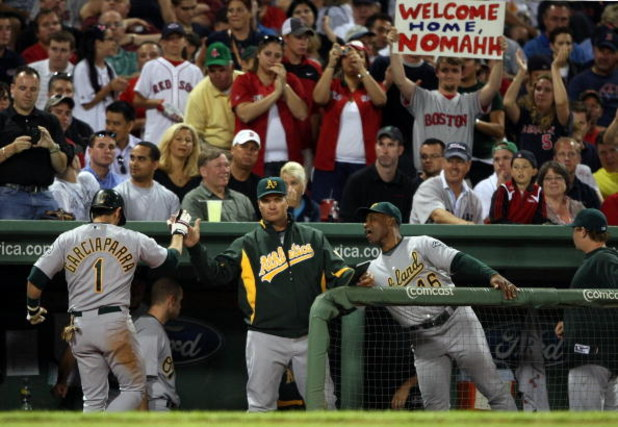 BOSTON - JULY 06:  Nomar Garciaparra #1 of the Oakland Athletics is congratulated by teammates in the dugout after he hit a single against the Boston Red Sox on July 6, 2009 at Fenway Park in Boston, Massachusetts. Garicaparra was pulled and Rajai Davis
