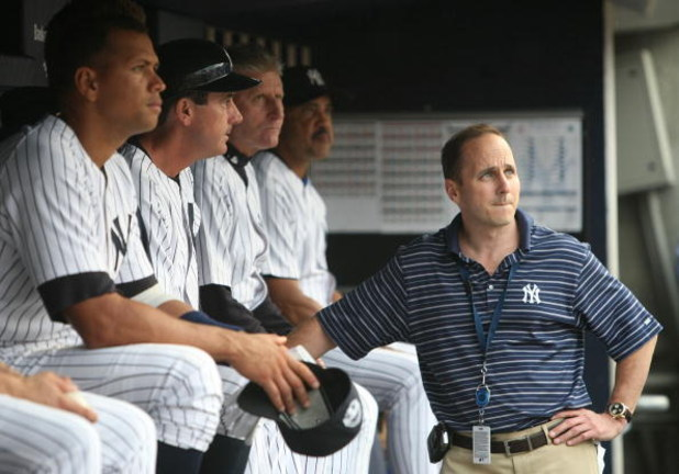 NEW YORK - JULY 2: Alex Rodriguez #2 (L) of the New York Yankees sits on the bench, joined by Yankees General Manager Brian Cashman (R) before a game against the Seattle Mariners at Yankee Stadium on July 2, 2009 in the Bronx borough of New York City.  (P