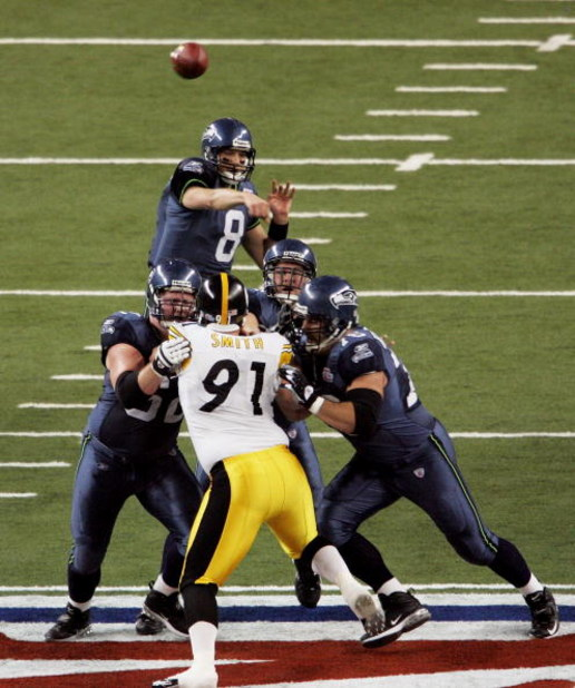DETROIT - FEBRUARY 05:  Quarterback Matt Hasselbeck #8 of the Seattle Seahawks throws a pass as his lineman triple-team defensive end Aaron Smith #91 of the Pittsburgh Steelers during the first quarter in Super Bowl XL at Ford Field on February 5, 2006 in