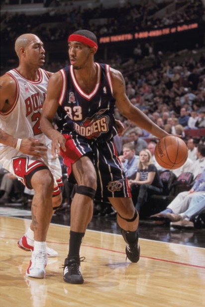 4 Dec 2001:  Houston Rocket forward Eddie Griffin #33 dribbles the ball past forward Marcus Fizer #21 of the Chicago Bulls during the NBA game at the United Center in Chicago, Illinois.  The Bulls crushed the Rockets 103-75. NOTE TO USER: User expressly a