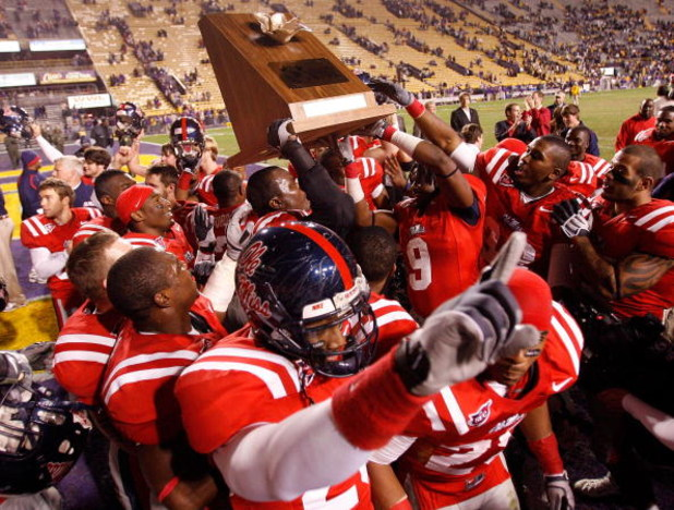 BATON ROUGE, LA - NOVEMBER 22:  Members of the Ole Miss Rebels celebrate with the 'Magnoila Bowl' trophy after defeating the Louisiana State University Tigers 31-13 on November 22, 2008 at Tiger Stadium in Baton Rouge, Louisiana.  (Photo by Chris Graythen