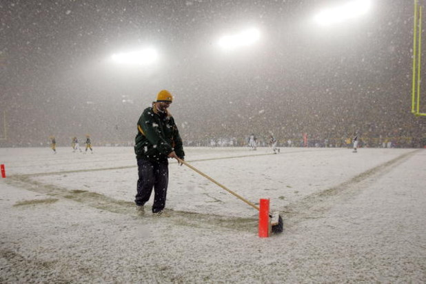 GREEN BAY, WI - JANUARY 12:  A field crew member sweeps the snow in the endzone during the game between the Green Bay Packers and the Seattle Seahawks during the NFC divisional playoff game on January 12, 2008 at Lambeau Field in Green Bay, Wisconsin.  (P