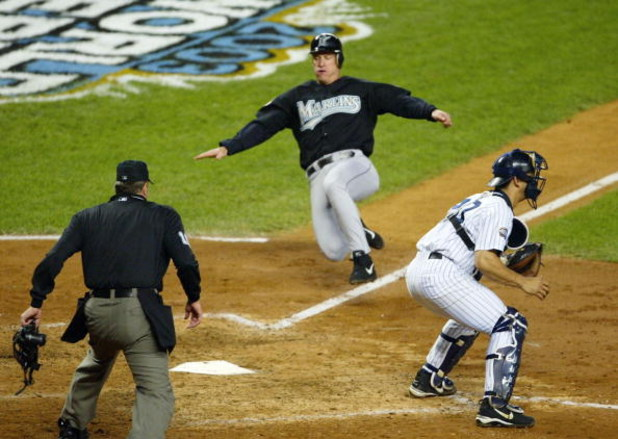 BRONX, NY - OCTOBER 25:  Jeff Conine #18 of the Florida Marlins scores on a sacrifice fly by teammate Juan Encarnacion #43 in the sixth inning against the New York Yankees during game six of the Major League Baseball World Series on October 25, 2003 at Ya