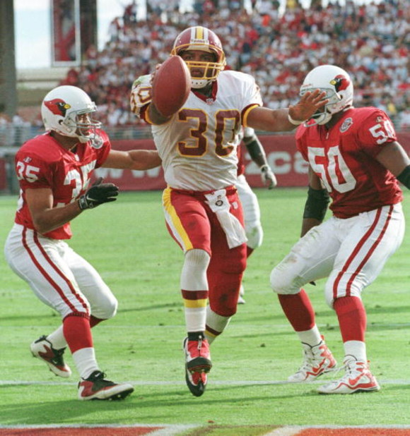 Washington Redskins runningback Brian Mitchell scores his team's second touchdown between Arizona Cardinals safety Aeneas Williams (35) and linebacker Tony McComb during the second quarter at Sun Devil Stadium in Tempe, Arizona, November 8, 1998. (Photo M
