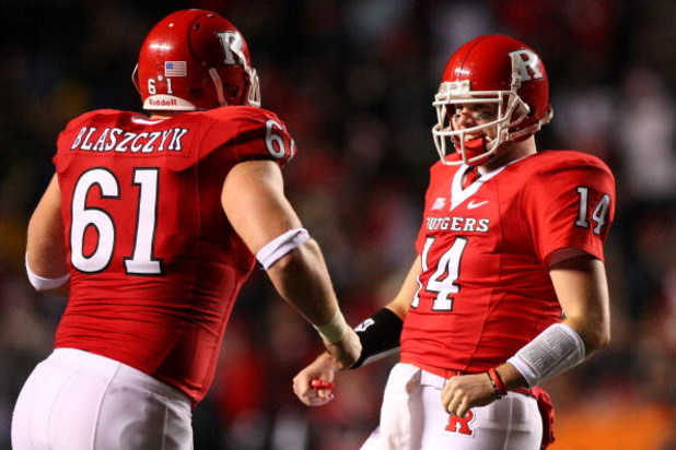 PISCATAWAY, NJ - DECEMBER 04:  Mike Teel #14 of the Rutgers Scarlet Knights (R) celebrates throwing the sixth touchdown pass with teammate Ryan Blaszczyk #61 during the second quarter of the game against the Louisville Cardinals at Rutgers Stadium on Dece