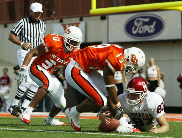 STILLWATER, OK - OCTOBER 30:  Punter Blake Ferguson #87 (R) of Oklahoma scrambles for the ball along with safety Jeremy Nethon #19 and safety Grant Jones #30 of Oklahoma State in the second quarter at Boone Pickens Stadium on October 30, 2004 in Stillwate