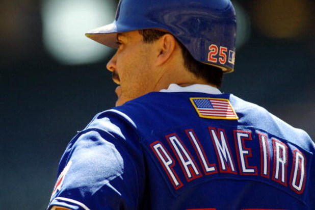 26 Sep 2001:  Rafael Palmeiro #25 of the Texas Rangers looks on during the game against the Seattle Mariners at The Ballpark in Arlington, Texas. Major League Baseball is currently wearing the American flag on the back of the uniform honoring the victims
