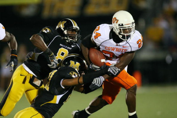 COLUMBIA, MO - OCTOBER 11:  Kendall Hunter #24 of the Oklahoma State Cowboys drags defenders of the Missouri Tigers for yardage on October 11, 2008 at Memorial Stadium in Columbia, Missouri.  (Photo by G. Newman Lowrance/Getty Images)