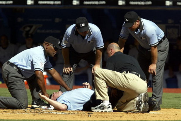 TORONTO - AUGUST 6:  Home plate umpire Marty Foster lies injured, suffering a contusion over his right knee after being hit by a broken bat in the second inning of the Toronto Blue Jays game against New York Yankees at Rogers Centre on August 6, 2005 in T