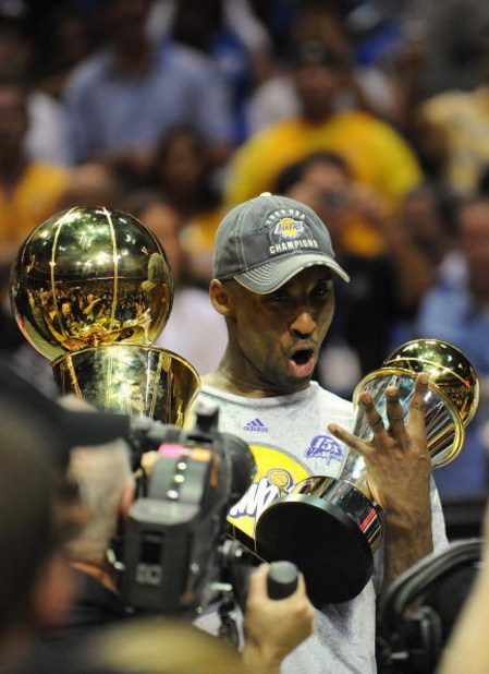 ORLANDO, FL - JUNE 14:  Kobe Bryant #24 of the Los Angeles Lakers holds the Bill Russell MVP trophy and the Larry O'Brien trophy after defeating the Orlando Magic in Game Five of the 2009 NBA Finals on June 14, 2009 at Amway Arena in Orlando, Florida. The