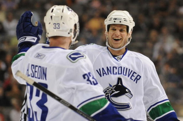 DALLAS - MARCH 24:  Henrik Sedin #33 of the Vancouver Canucks celebrates his goal with Kevin Bieksa #3 during play against the Dallas Stars at the American Airlines Center on March 24 , 2009 in Dallas, Texas.  (Photo by Ronald Martinez/Getty Images)