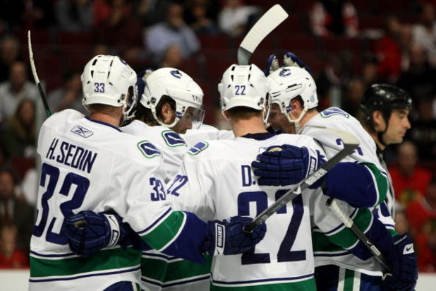 CHICAGO - MAY 05:  (L-R) Henrik Sedin #33, Steve Bernier #18, Daniel Sedin #22 and Alexander Edler #23 of the Vancouver Canucks celebrate after Bernier scored a goal in the third period against the Chicago Blackhawks during Game Three of the Western Confe