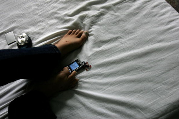 KUNMING, CHINA - SEPTEMBER 7: (CHINA OUT) A disabled girl writes a text message on her mobile phone with her foot in her dormitory at the South of the Clouds Swimming Club on September 7, 2007 in Kunming of Yunnan Province, China. The club, the first of i