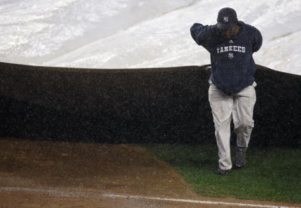 NEW YORK - SEPTEMBER 11:  A member of the grounds crew pulls the tarp over the infield in the 7th inning during a rain delay for the New York Yankees game against the Baltimore Orioles on September 11, 2009 at Yankee Stadium in the Bronx borough of New Yo