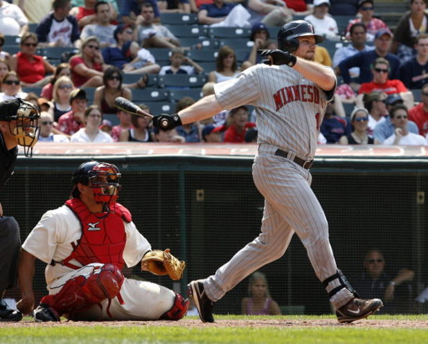CLEVELAND - JULY 27:  Jason Kubel #16 of the Minnesota Twins hits a single in the ninth inning to score Justin Morneau in front of Sal Fasano #44 of the Cleveland Indians on July 27, 2008 at Progressive Field in Cleveland, Ohio. Minnesota won the game 4-2