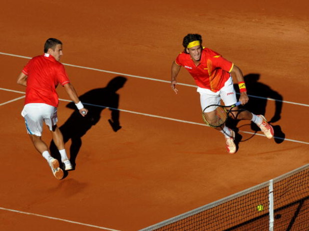 BENIDORM, SPAIN - MARCH 07:  Feliciano Lopez (R) of Spain hits the ball against the net flanked by his doubles partner Tommy Robredo during their doubles match against Nenad Zimonjic and Viktor Troicki of Serbia on day one of the Davis Cup World Group fir